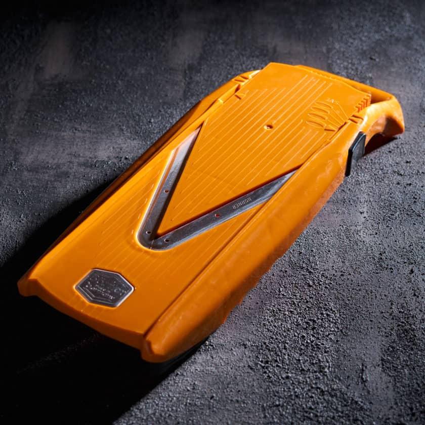 Orange mandoline on a black surface with dramatic lighting