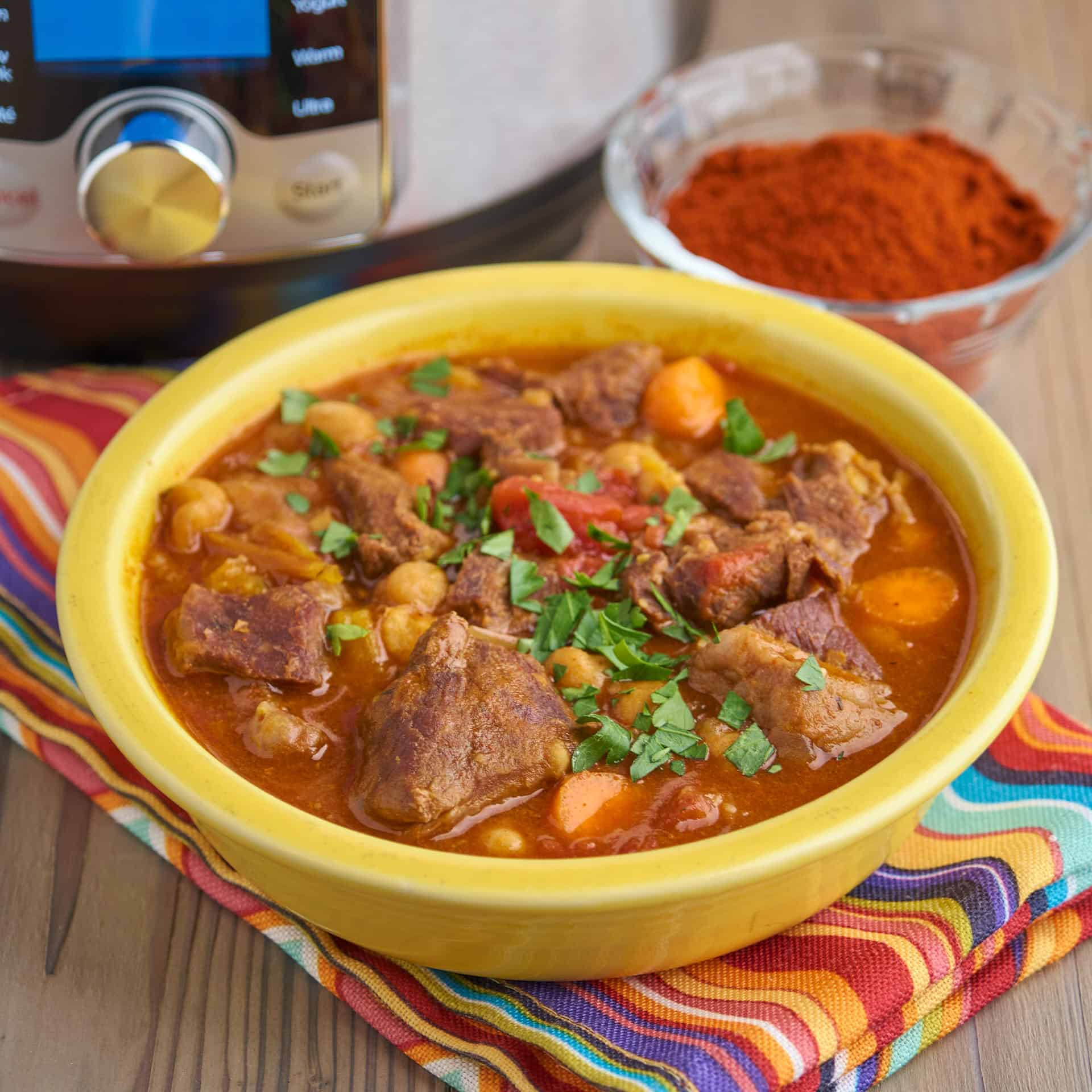 A bowl of Spanish beef stew in front of a dish of smoked spanish paprika - pimenton de la Vera - and an Instant Pot