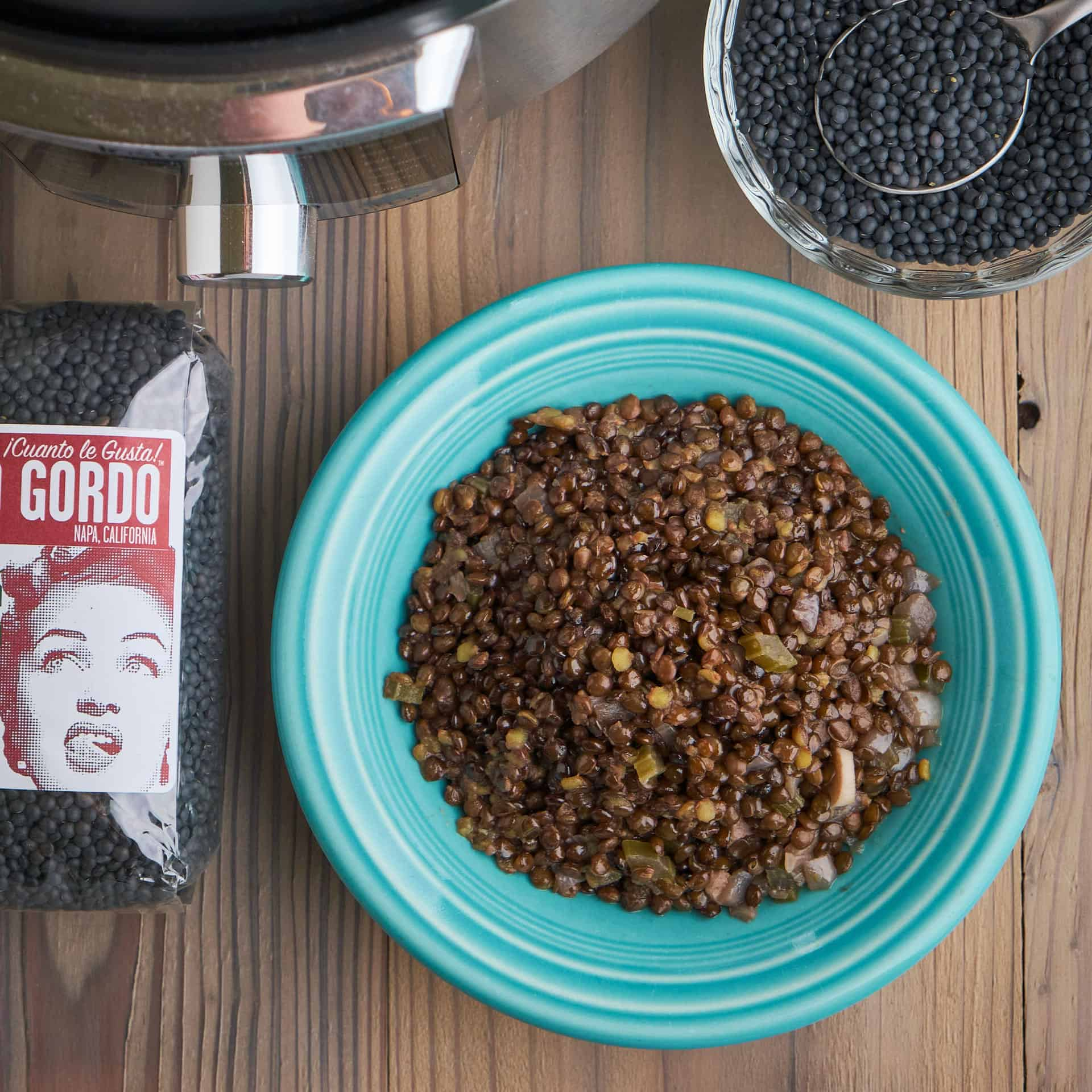 A bowl of cooked beluga lentils, next to a bowl and bag of uncooked lentils, and an Instant Pot