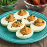 Sun-dried tomato deviled eggs on a plate, sprinkled with basil, with basil leaves and sun-dried tomatoes in the background.