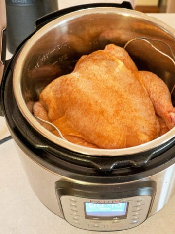A whole chicken sprinkled with Cajun Spice Rub in an Instant Pot, ready to cook
