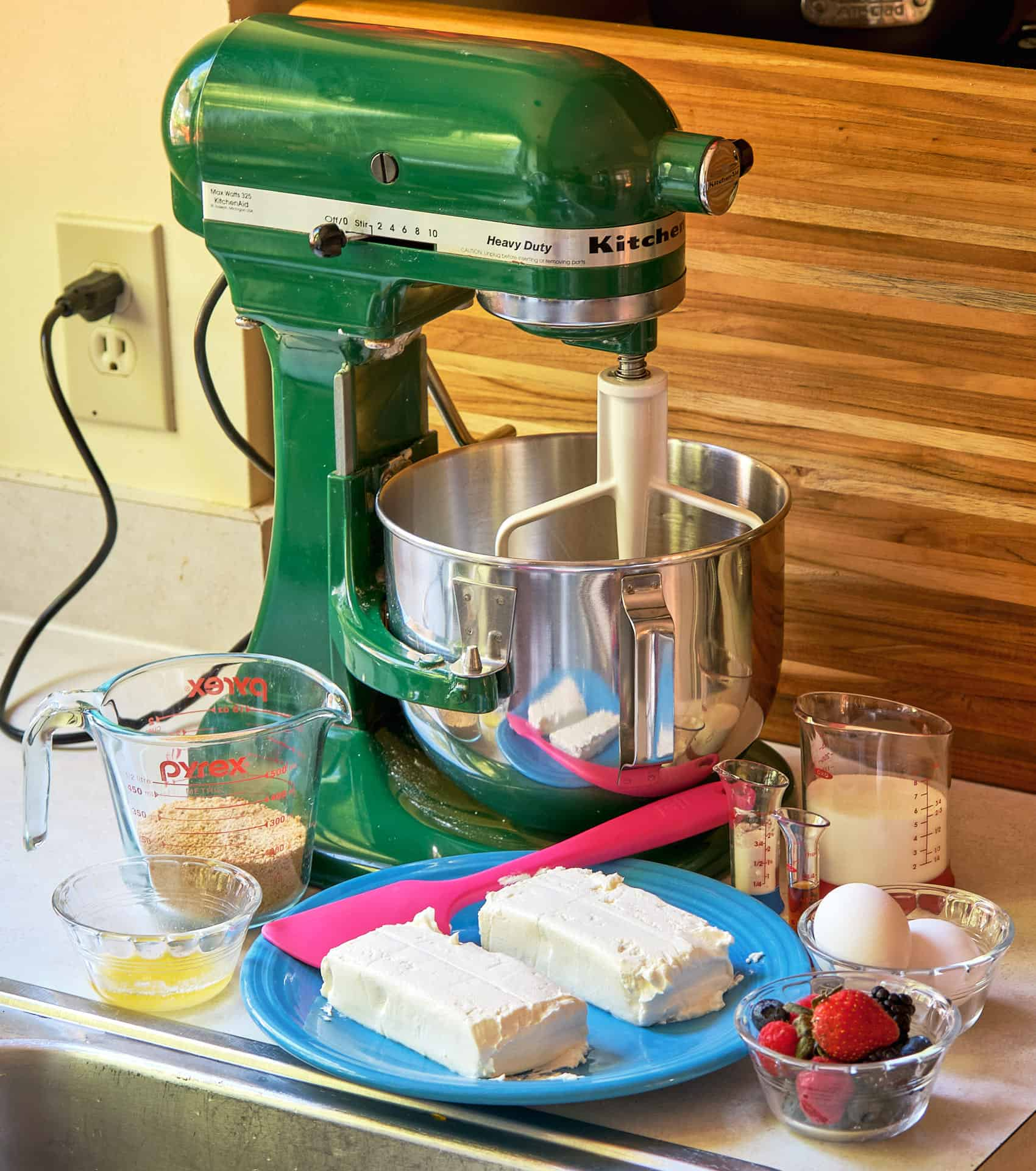 A green stand mixer in front of plates, bowls, and measuring cups holding the ingredients for berry cheesecake