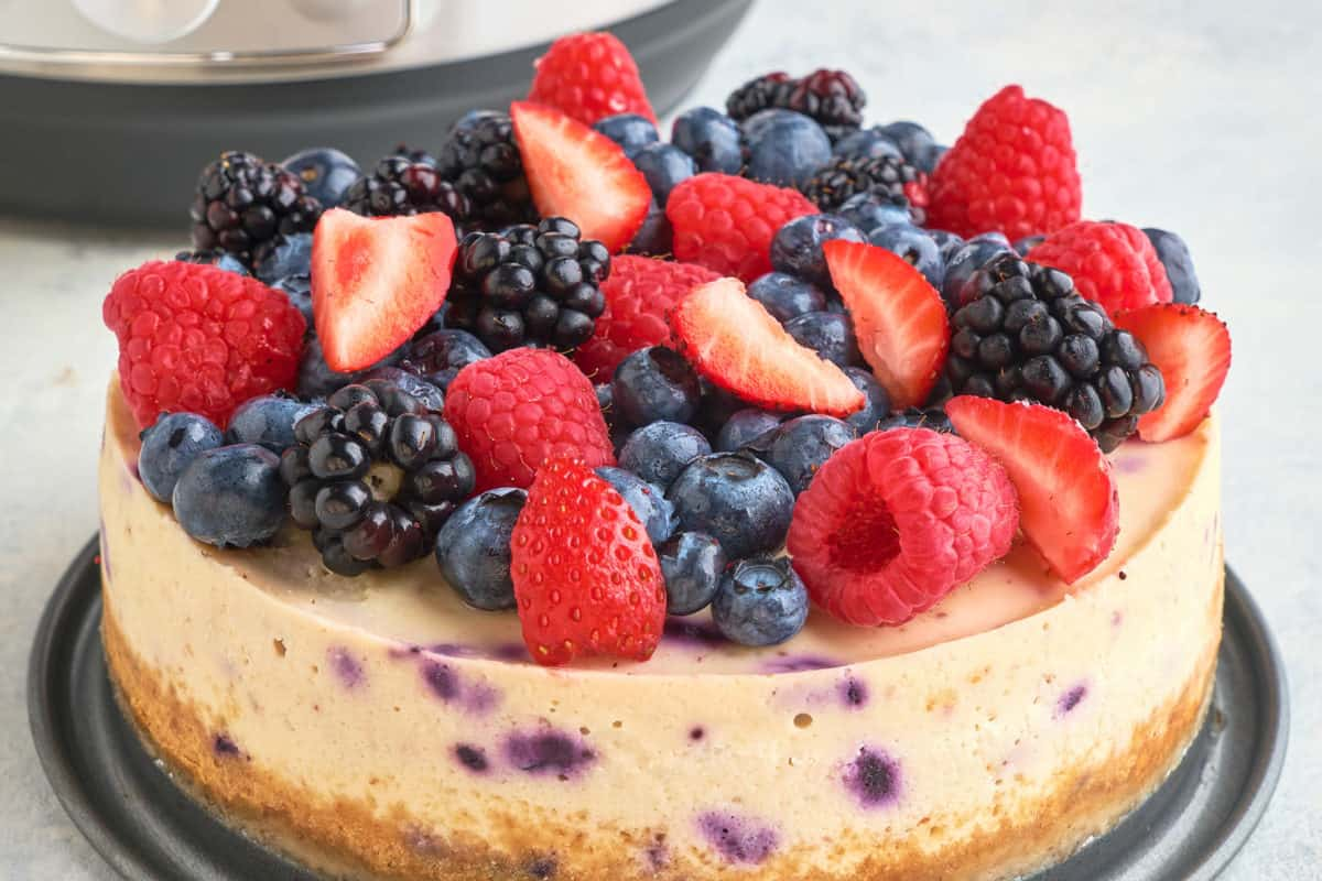 A berry cheesecake in front of an Instant Pot