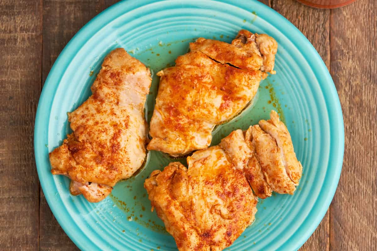 A plate of cooked chicken thighs, with an Instant Pot and a jar of paprika