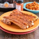 Spanish ribs on a yellow plate with smoked paprika, chickpeas, and an Instant Pot in the backgroud