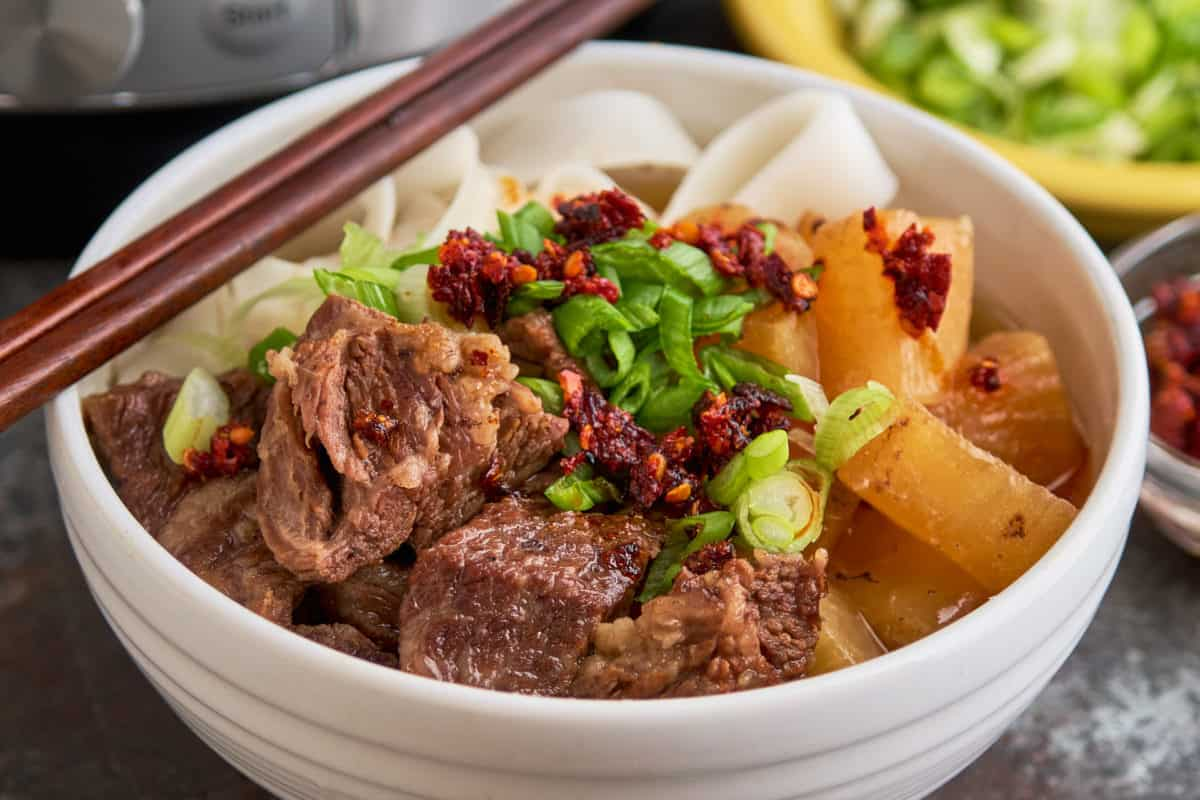 A bowl of Chinese beef noodle soup, with green onions and chili crisp