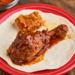 An Ethiopian chicken drumstick, coated with sauce, on a tortilla on a red plate