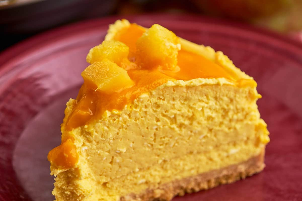 A slice of mango cheesecake on a maroon plate