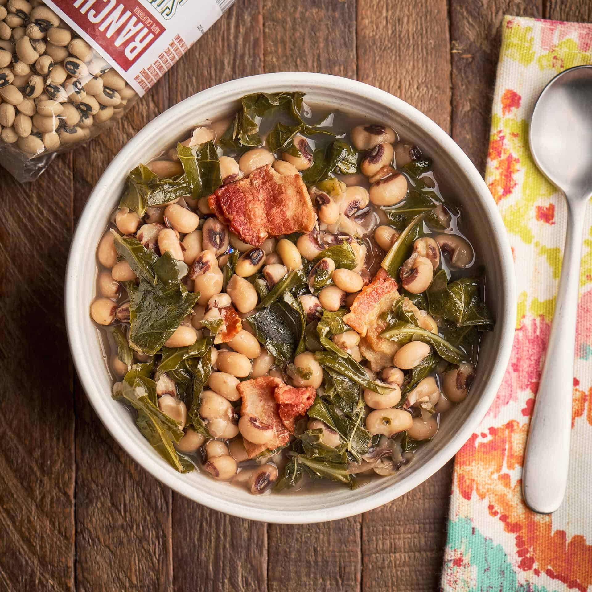 A bowl of black eyed peas and collard greens on a wood table with a bag of beans, a napkin, and a spoon