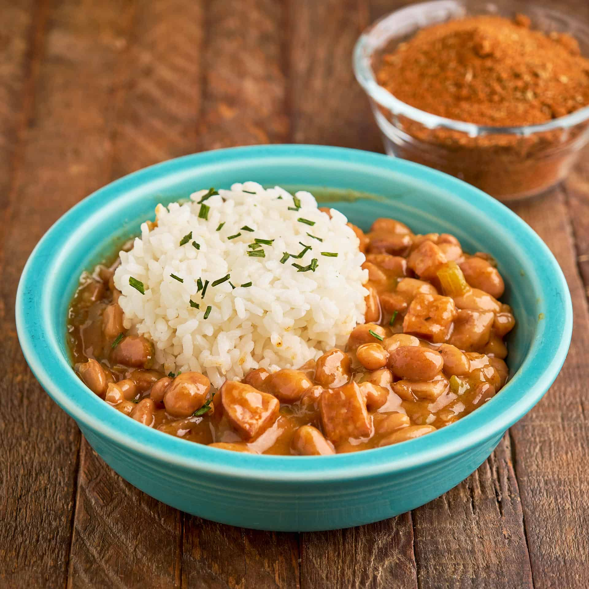 A bowl of Cajun pinto beans and rice, with a smaller bowl of spices behind them