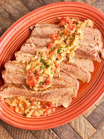 A platter of sliced brisket, covered with onions and tomatoes, on a wood table