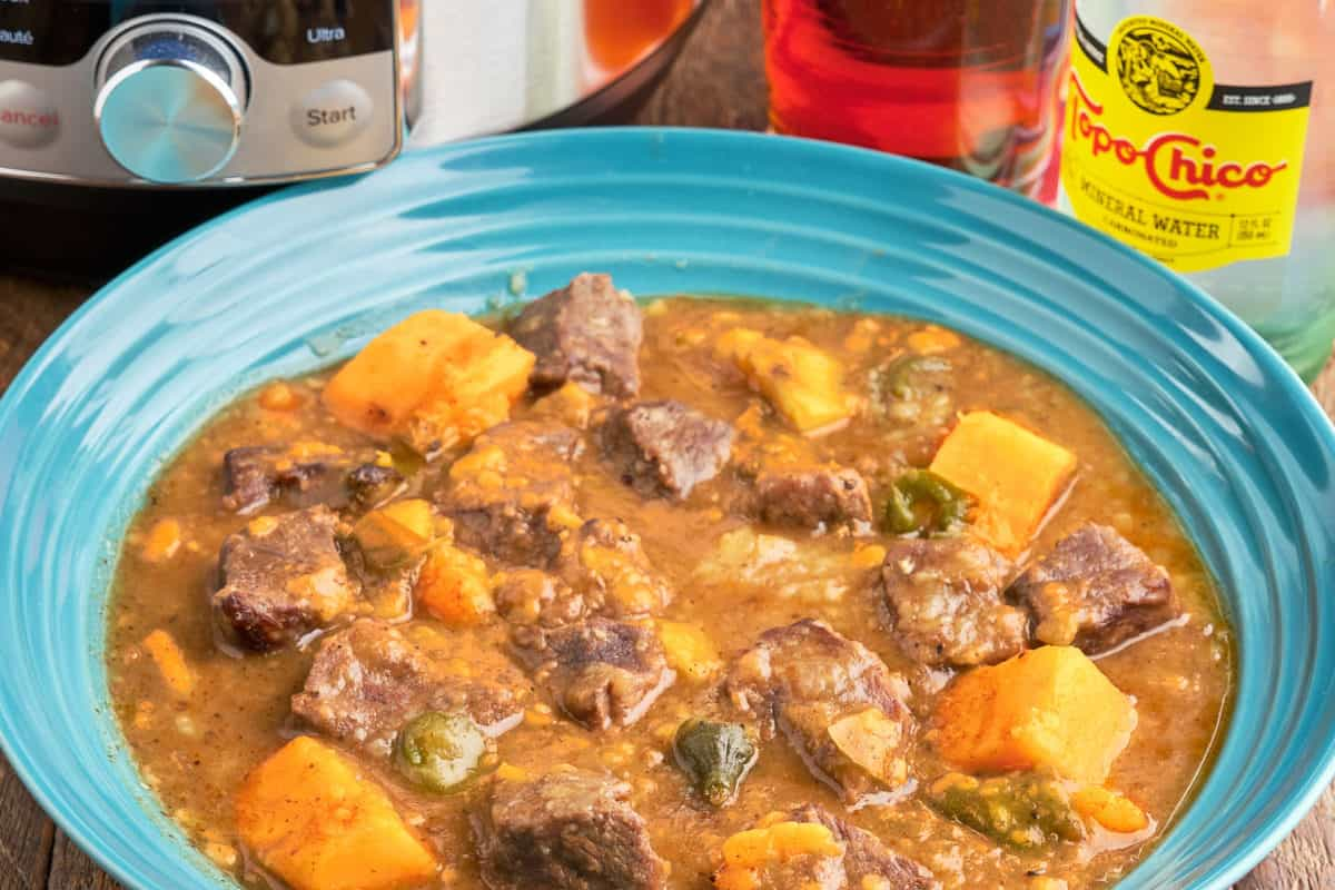 A bowl of beef stew with sweet potatoes and jalapeños, with an Instant Pot, a glass of beer, and a bottle of Top Chico in the background