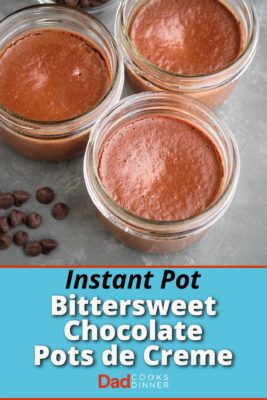 Three bittersweet chocolate pots de creme, with some chocolate chips on a gray tbable