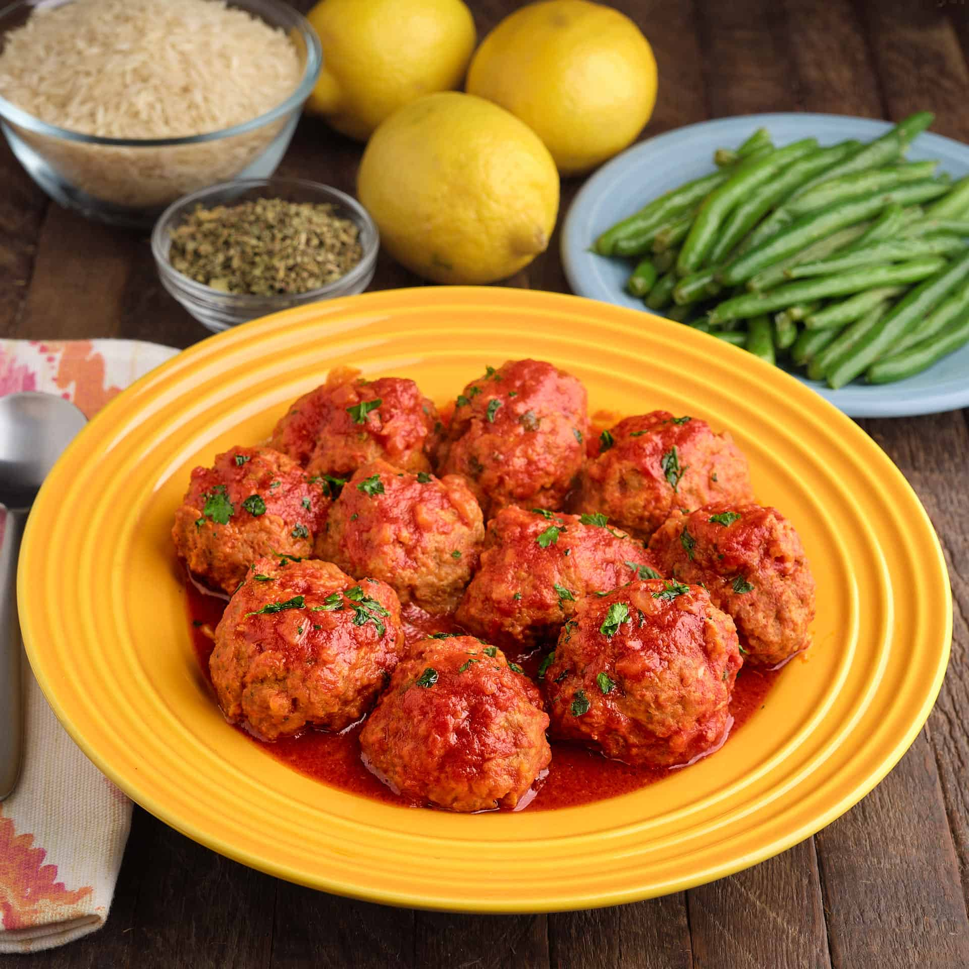A plate of Greek meatballs in tomato sauce, with green beans, lemons, oregano, and rice in the background