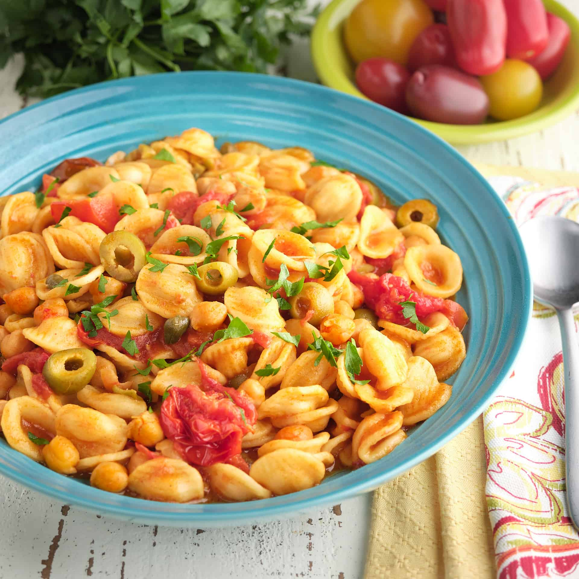 A bowl of chickpea puttanesca with orecchiette, with tomatoes, parsley, napkins, and a spoon