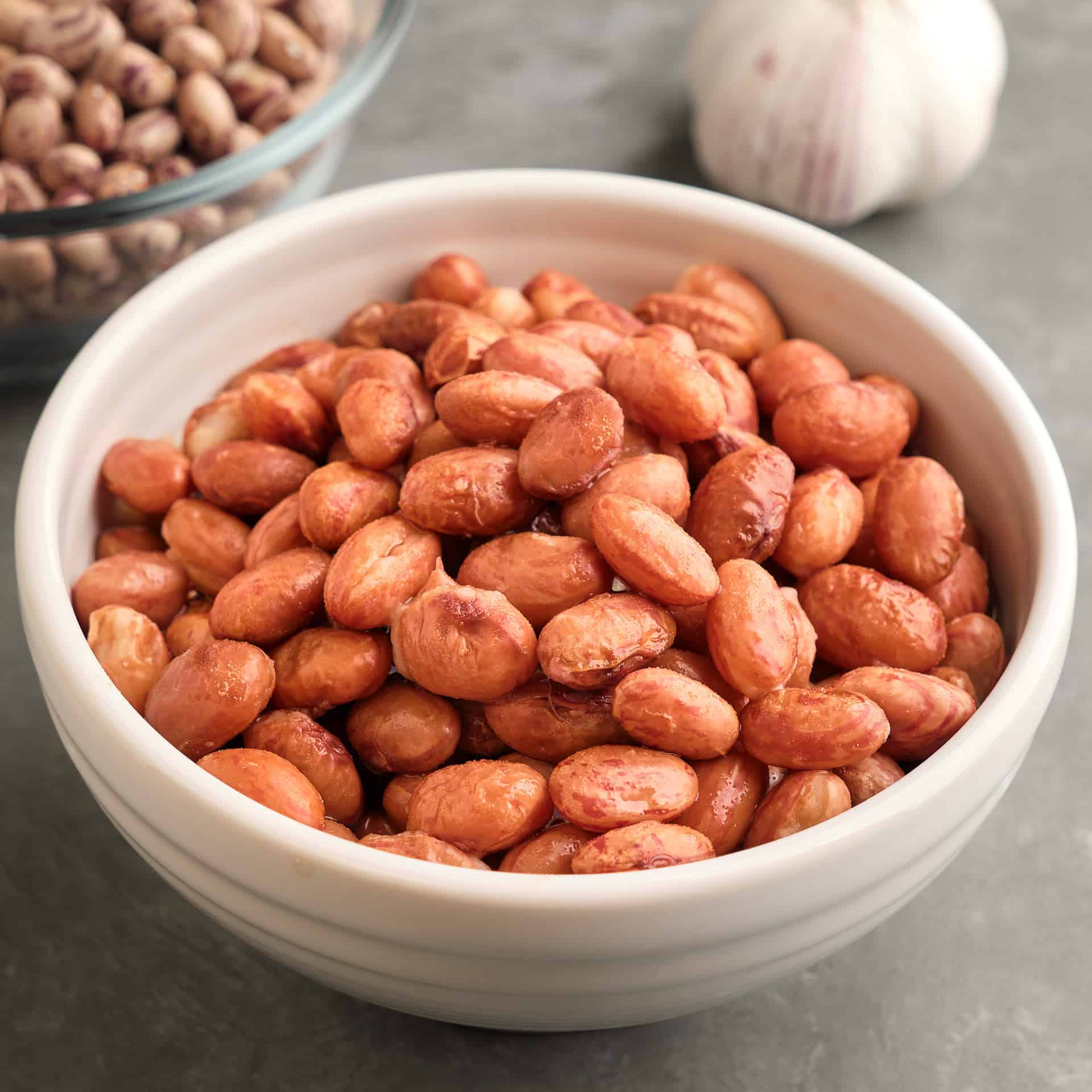A bowl of cranberry beans, with a head of garlic and another bowl of dried cranberry beans in the background