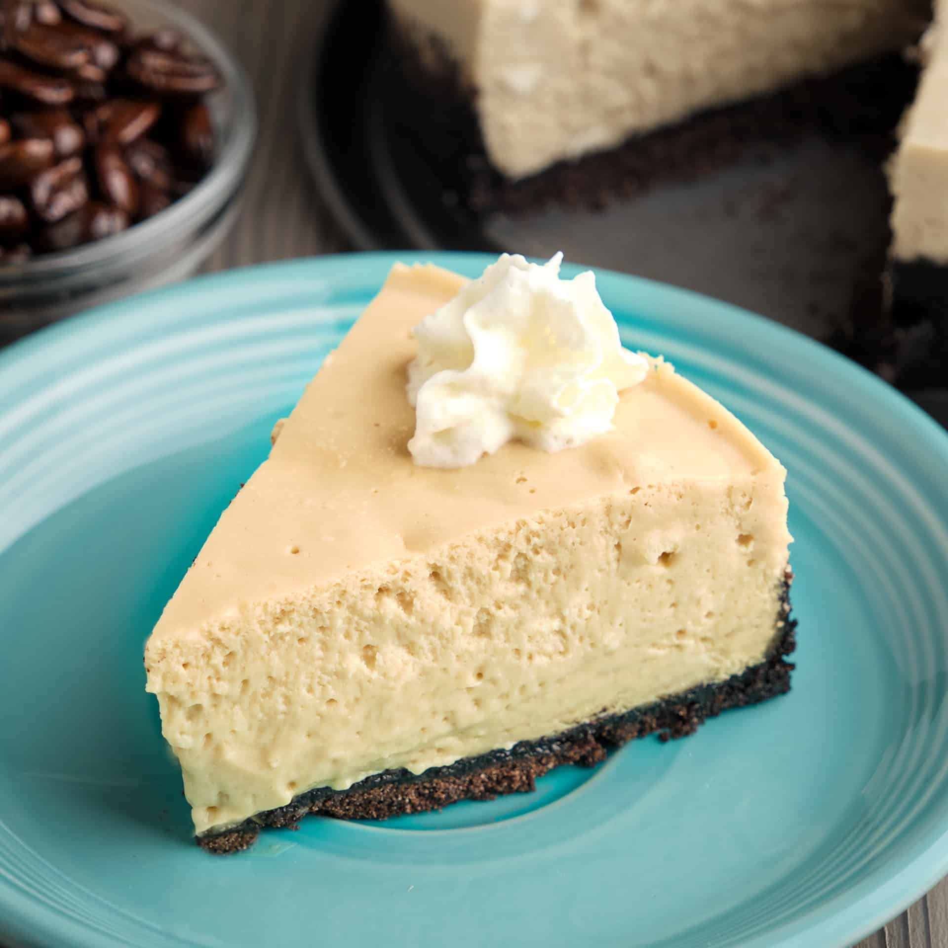 A slice of espresso cheesecake topped with whipped cream