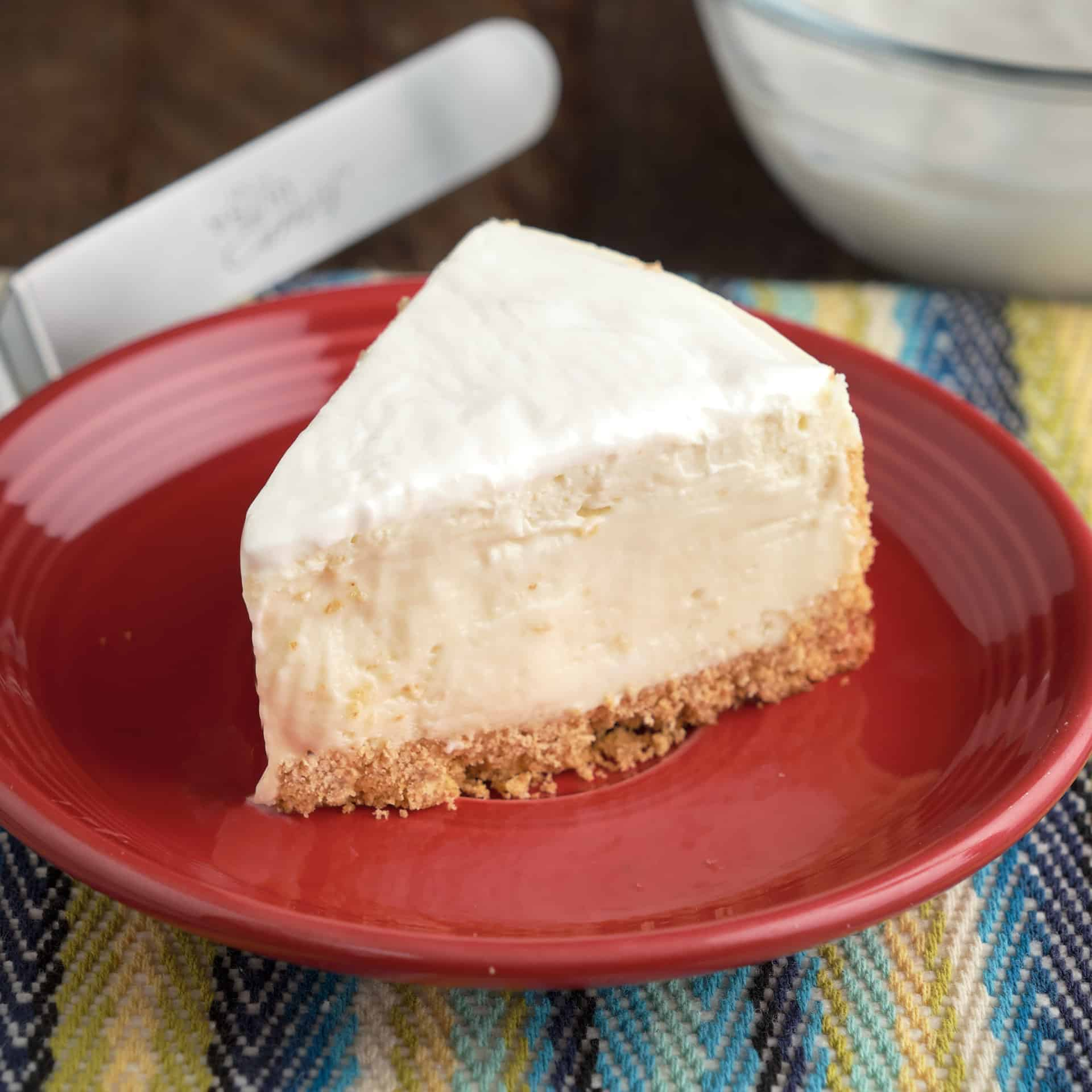 A slice of cheesecake with sour cream topping