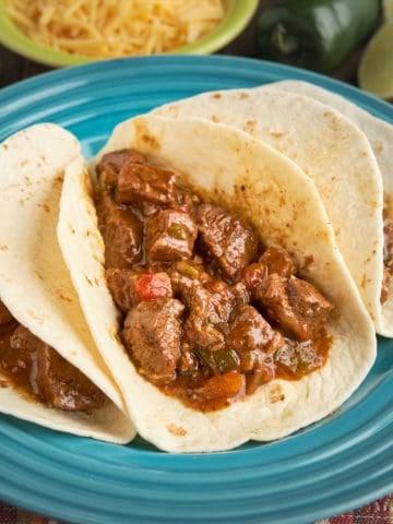 A plate of three carne guisada tacos