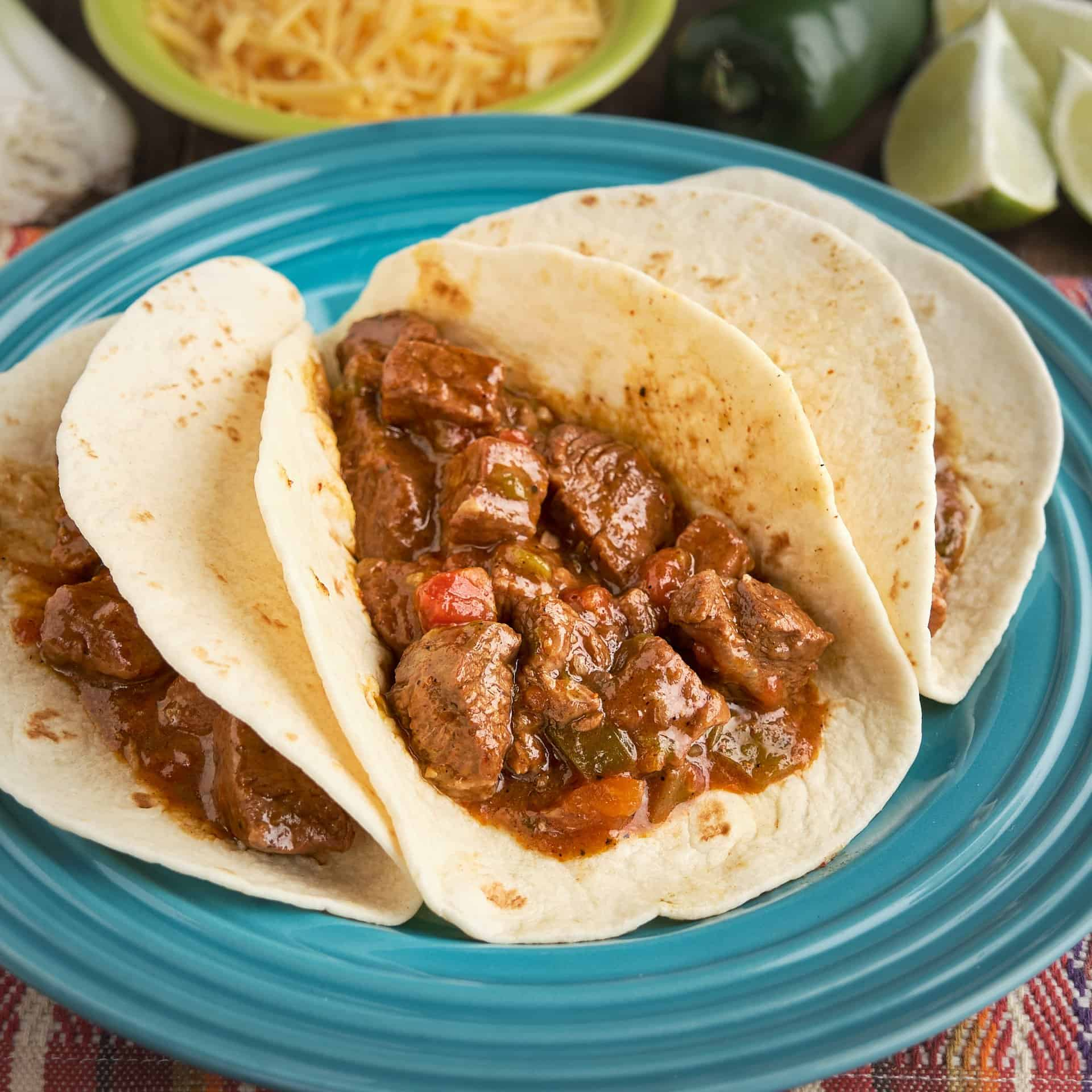 A plate of three carne guisada tacos