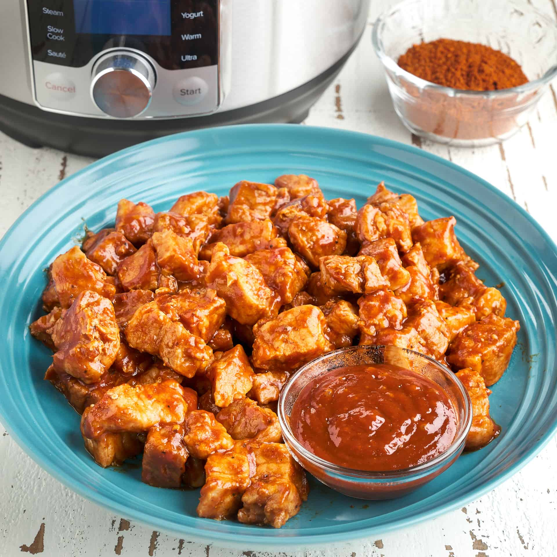 A bowl of pork belly cubes, tossed in barbecue sauce, with a small bowl of barbecue sauce, a bowl of barbecue rub, and a pressure cooker in the background