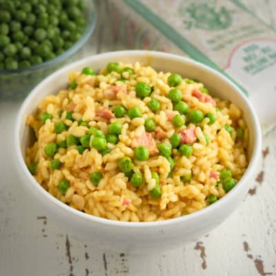 A bowl of rice and peas with more peas and a bag of vialone nano rice in the background
