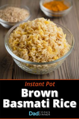 A bowl of brown basmati rice with uncooked rice and ground turmeric in the background