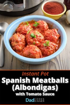A bowl of Spanish meatballs (Albondigas) in tomato sauce, with a pressure cooker and smoked paprika in the background.