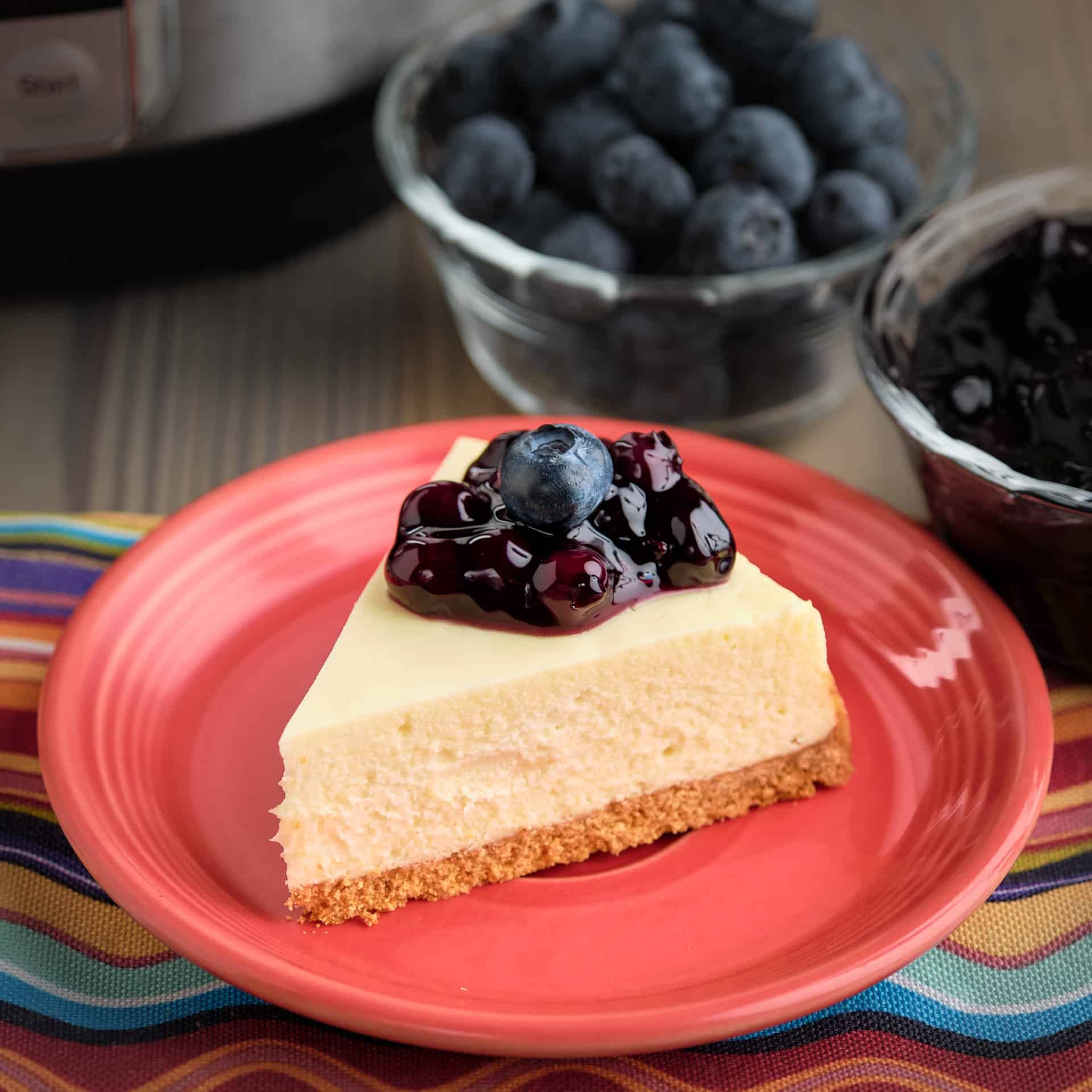 A slice of goat cheese cheesecake topped with blueberries
