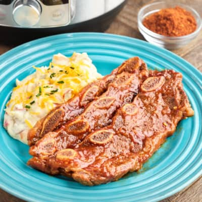 A plate with BBQ short ribs and mashed potatoes, with a dish of BBQ rub and a pressure cooker in the background