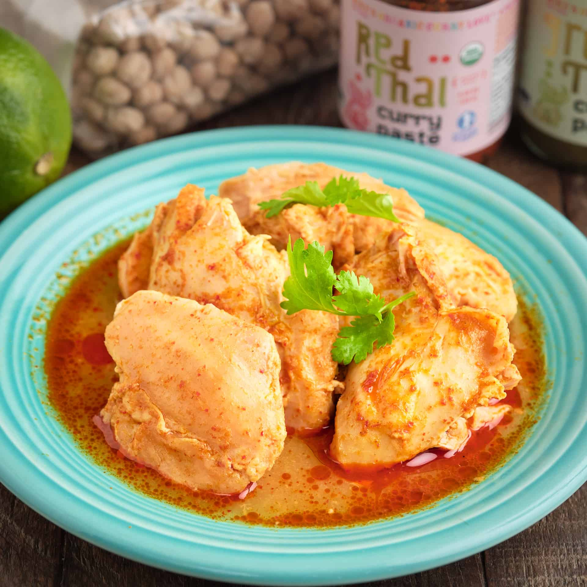 A plate of coconut curry chicken thighs with Thai curry paste and a lime in the background