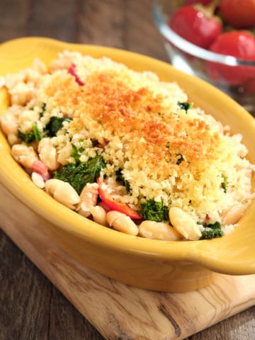 A gratin dish of beans, greens, and cherry peppers, topped with a toasted bread crumb crust, with more cherry peppers in the background
