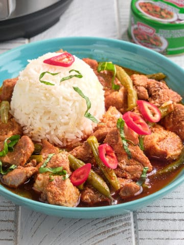 A bowl of prik king pork curry with a scoop of rice, topped with slivered basil and Thai red peppers